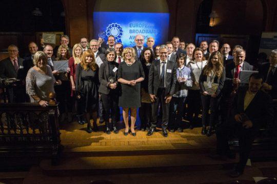 Viele lächelnde Menschen stehen zusammen und halten Ihre Auszeichnung des European-Broadband-Awards 2017 hoch.